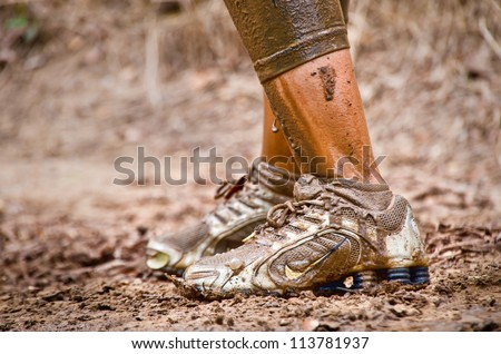 DALLAS, TEXAS - SEPTEMBER 15: Closeup of unidentified race participant's muddy feet at a mud pit in the Dash of the Titans Mud Run Race on September 15, 2012 in Dallas, Texas. - stock photo