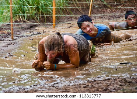 DALLAS, TEXAS - SEPTEMBER 15: Unidentified participants crawl through a mud pit in the Dash of the Titans Mud Run Race on September 15, 2012 in Dallas, Texas. - stock photo
