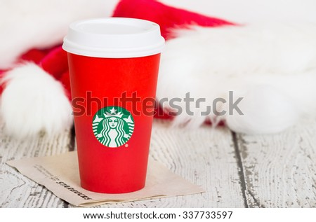 DALLAS, TX - NOVEMBER 10, 2015: A cup of Starbucks popular holiday beverage, served in the new 2015 designed red holiday cup. Displayed on white rustic table with Christmas hats in the background.  - stock photo