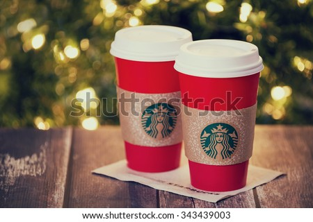 DALLAS, TX - NOVEMBER 24, 2015: A cup of Starbucks popular holiday beverage, served in the new 2015 designed red holiday cup. Displayed on rustic table against Christmas tree lights background.  - stock photo