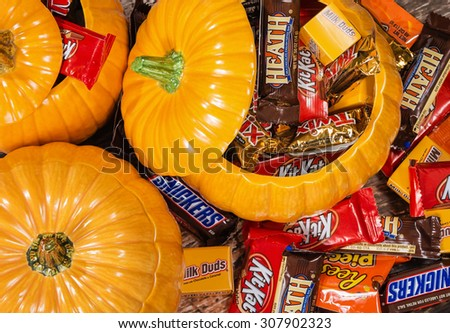 DALLAS, TX - OCTOBER 31, 2014: Decorative pumpkins filled with assorted Halloween chocolate candy made by Mars, Incorporated and the Hershey Company. - stock photo