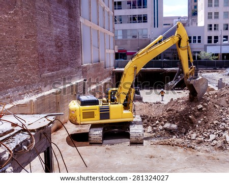 Dallas, TX USA May 2015: Large, tracked, backhoe clearing the basement area of a demolished building in the central business district in downtown Dallas - stock photo