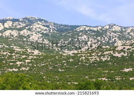 Dalmatian coast mountains spotted with limestone rocks and green bushes, Croatia - stock photo