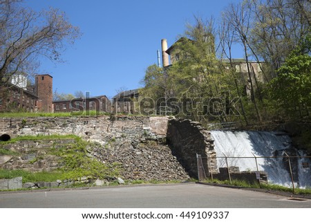 Dam and stone wall ruins below the Amerbelle, Hockanum and Dart's Stone Mills complex in Rockville, Connecticut. - stock photo