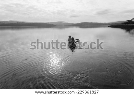 Dam Canoe Landscape Black White Vintage Boy girl paddle out in canoe kayak on smooth dam water landscape  in black white vintage - stock photo