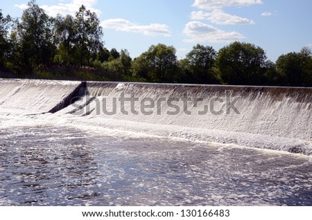 dam construction on river and summer waterfall - stock photo