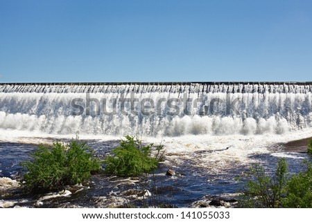 Dam overflow of water on the man-made storage pond - stock photo