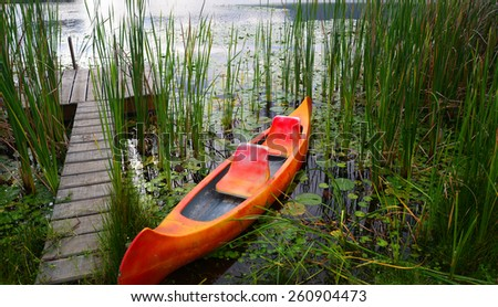 Dam with jetty and canoe in the Garden Route, South Africa - stock photo