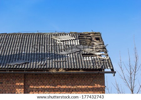 Damaged asbestos roofing material - stock photo
