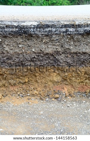 Damaged asphalt. Layer of clay that were eroded under the asphalt. - stock photo