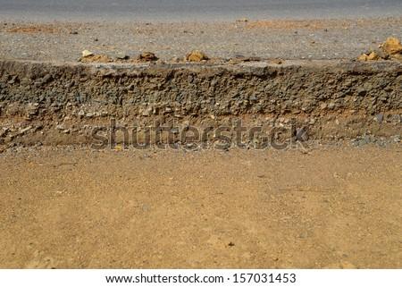 Damaged asphalt. Layer of clay that were eroded under the asphalt.  - stock photo