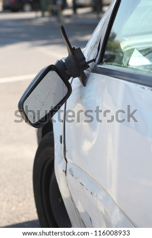 Damaged car and broken side rear view mirror. Vertical composition. - stock photo