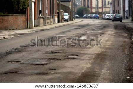 Damaged car road with a lot of cracks closeup - stock photo