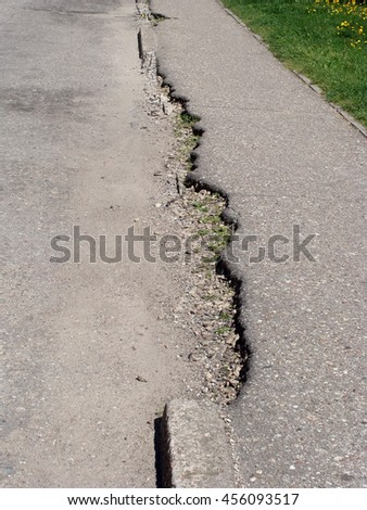 Damaged crushed asphalt sidewalk or footpath border close up.                        - stock photo
