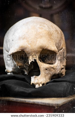 Damaged human skull and old book. Scratched pattern. - stock photo