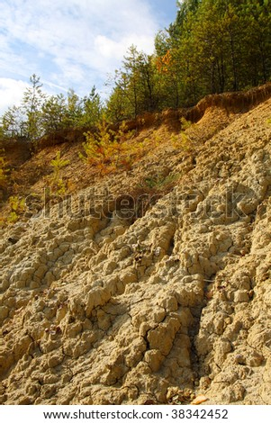 Damaged landscape of mud deeply cracked by erosion of the rain - stock photo