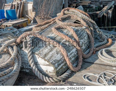 Damaged moss covered rowboat with colorful hemp hawser rope sitting atop of it on a working dock in New England - stock photo