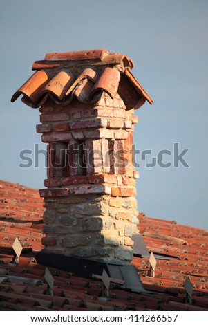 Damaged old brick fireplaces in the house roof - stock photo