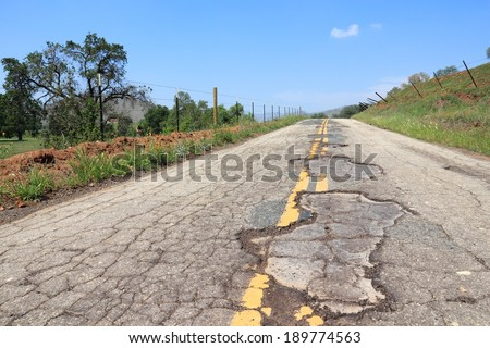 Damaged road of Yokohl Drive in California, USA - cracked asphalt blacktop with potholes and patches - stock photo