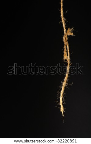 damaged rope on black background - stock photo