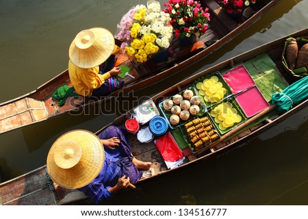 DAMNOEN SADUAK ,THAILAND-APRIL 5:Damnoen Saduak Floating  Market on April 5,2008 in Thailand.Featuring many small boats laden with colourful fruits, vegetables and Thai cuisine. - stock photo