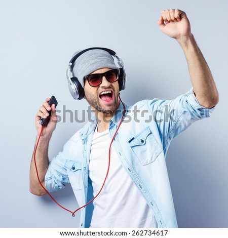 Dance! Handsome young stylish man in headphones holding MP3 Player and dancing while standing against grey background - stock photo