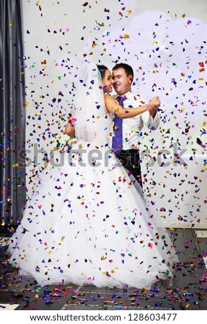 Dance of bride and groom in multi-colored confetti flying - stock photo