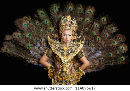 dancer in a golden dress with peacock feathers - stock photo