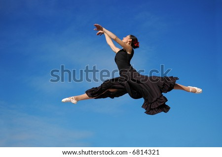 Dancer jumping against blue sky wearing black - stock photo
