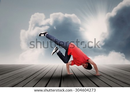 Dancer posing on a wooden floor with clouds and sunlight background - stock photo