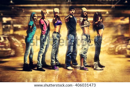 Dancer team pointing handsign to camera. Urban underground parking interior with light explosion effect. - stock photo