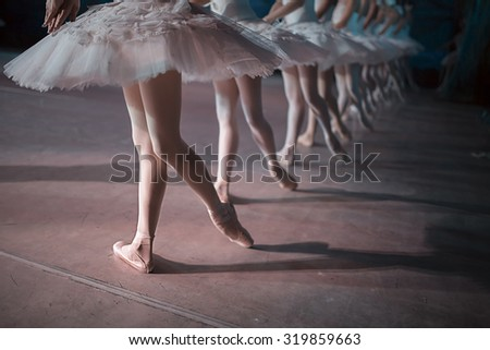 Dancers in white tutu synchronized dancing on stage. Repetition. - stock photo
