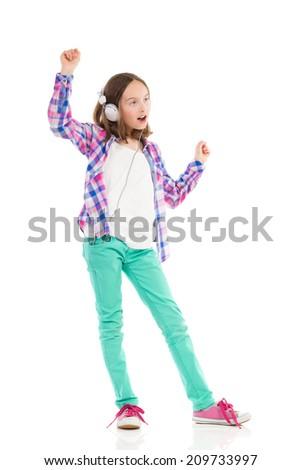 Dancing girl with headphones. Full length studio shot isolated on white. - stock photo