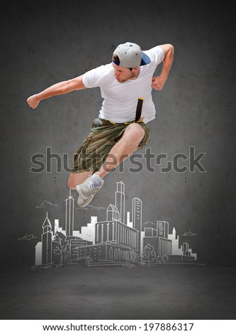 dancing, happiness and people concept - male dancer jumping in the air with city drawing in the back - stock photo