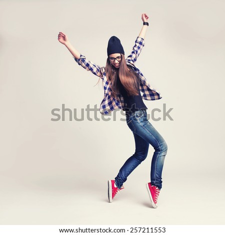 Dancing hipster girl in glasses and black beanie on light background - stock photo