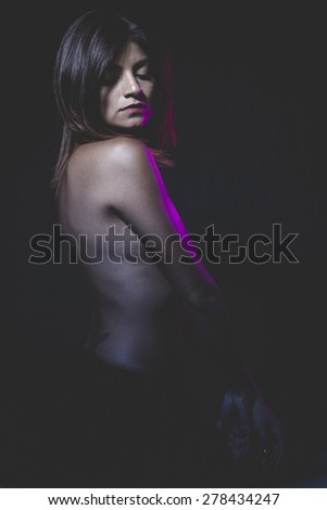 Dancing, latina naked ballerina in a black tutu and pink light - stock photo