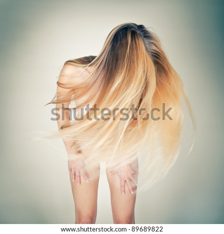 Dancing nude woman shacking her long blond hair, toned photo - stock photo