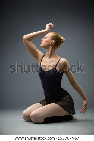 Dancing on the floor ballerina with her eyes closed, isolated on grey. Concept of elegant art and sportive hobby - stock photo