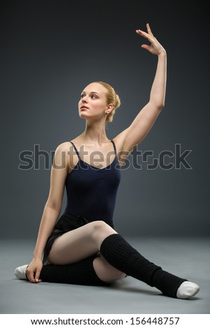 Dancing on the floor ballerina with her hand up, isolated on a white background on grey. Concept of elegant art and sportive hobby - stock photo