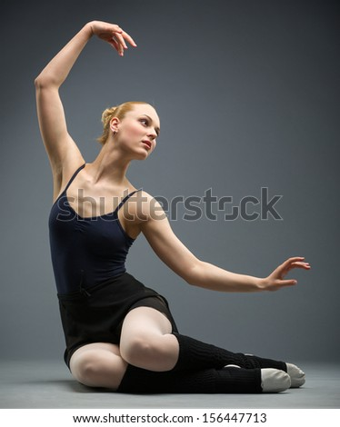 Dancing on the floor ballerina with her hand up, isolated on grey. Concept of elegant art and sportive hobby - stock photo