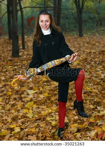 Dancing pretty young girl with yellow umbrella in fall forest - stock photo