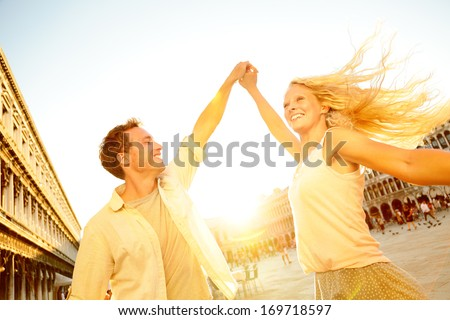Dancing romantic couple in love in Venice, Italy on Piazza San Marco. Happy young couple having fun in dance on travel vacation on St Mark's Square. Beautiful blonde woman, handsome man in their 20s. - stock photo