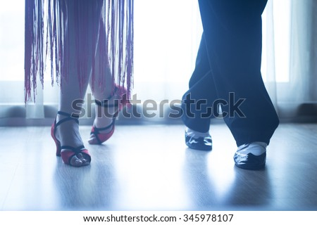 Dancing shoes feet and legs of female and male couple ballroom and latin salsa dancer dance teacher in dance school rehearsal room class. - stock photo