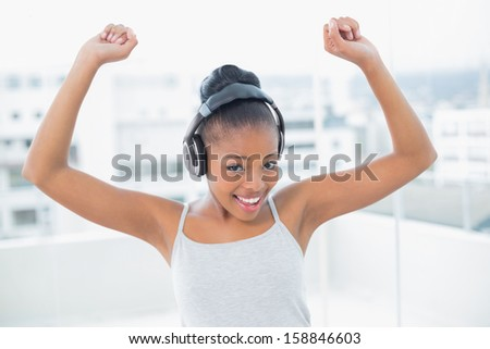 Dancing woman listening to music with headphones while looking at camera - stock photo