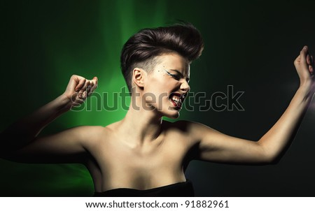 dancing woman with red lips in green light - stock photo