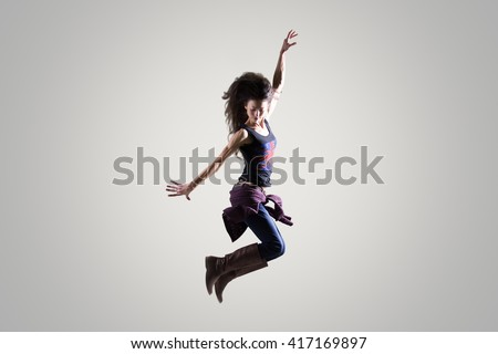 Dancing young woman portrait. Fit sporty girl wearing English flag tank top warming up, working out and jumping in the air with her long hair flying. Studio image. Grey background - stock photo