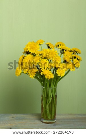 dandelion flowers in a glass on a wooden background - stock photo