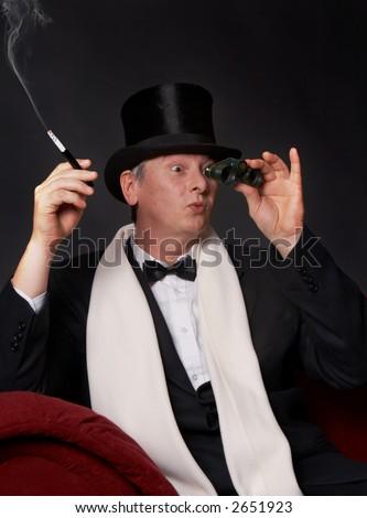 Dandy figure looking through his opera glasses - stock photo