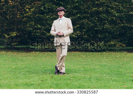 Dandy standing on lawn with tall hedge. - stock photo