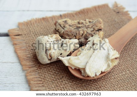 dang gui (angelica sinensis) with dang gui ginseng slice on wooden spoon, traditional chinese herbal medicine. - stock photo